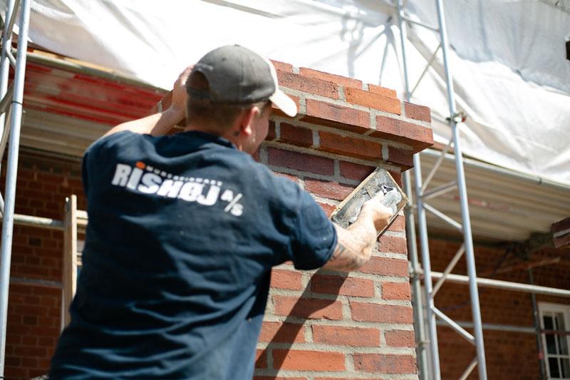 Håndværker i gang med omfugning af murværk